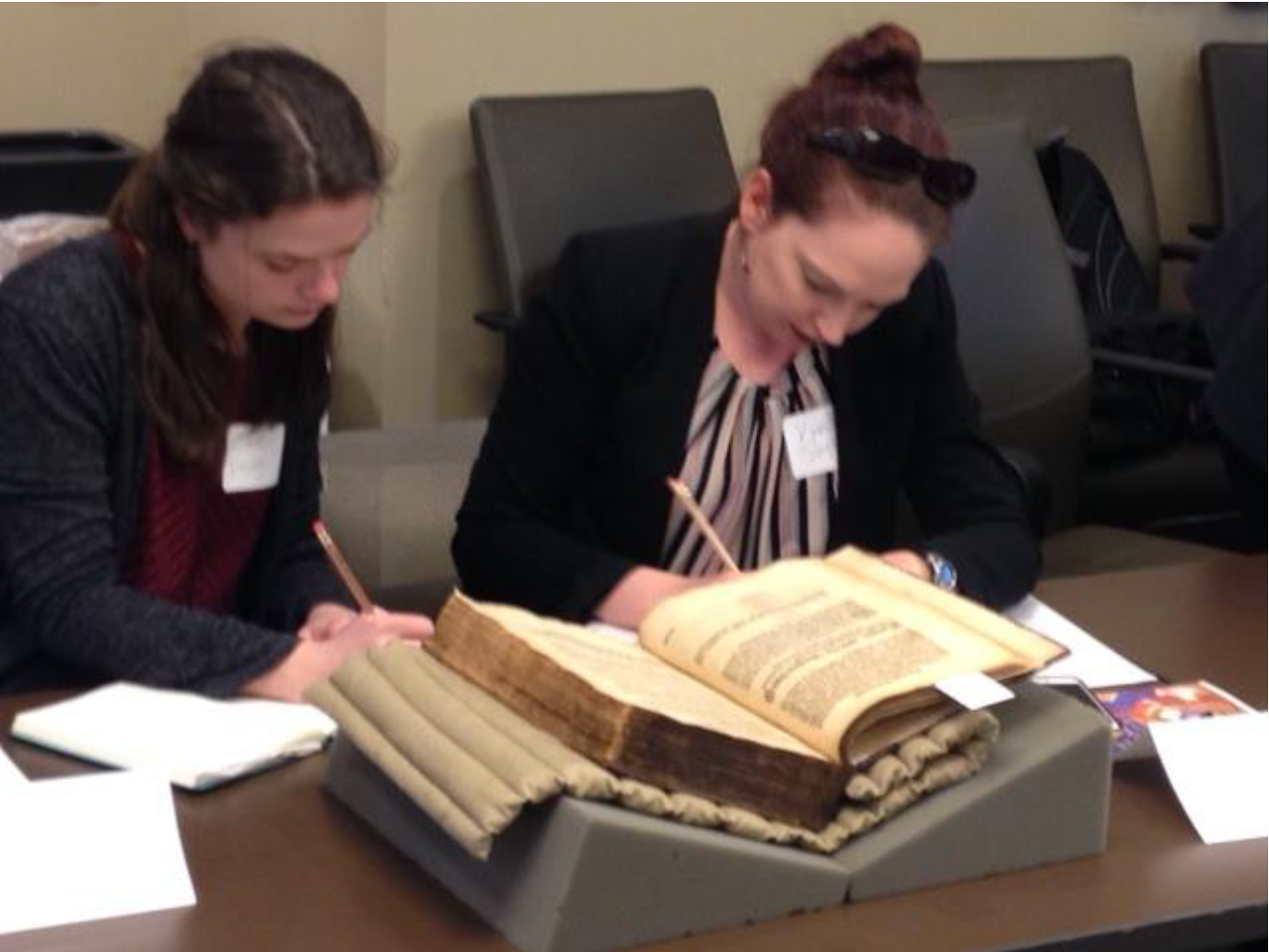 "Workshop participants (above and below) examine early modern volumes, noting features that ""tell a story about the book."""